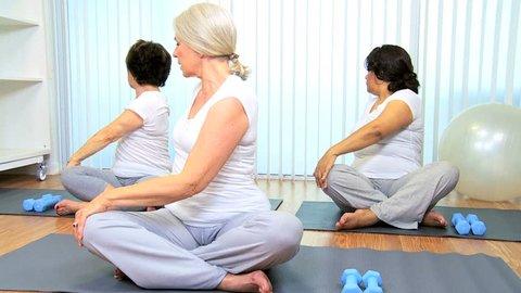 Three multi ethnic retired ladies exercising senior yoga class