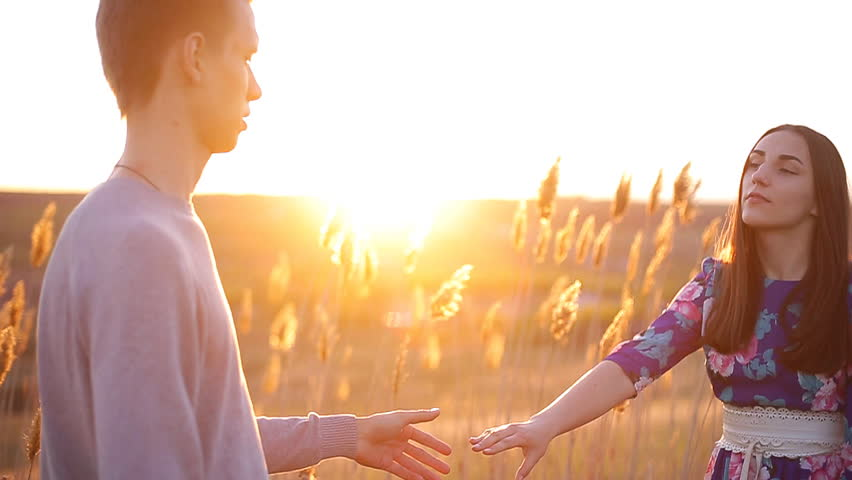 Guy and girl at sunset kissing in the field on a summer evening | Shutterstock HD Video #26990773