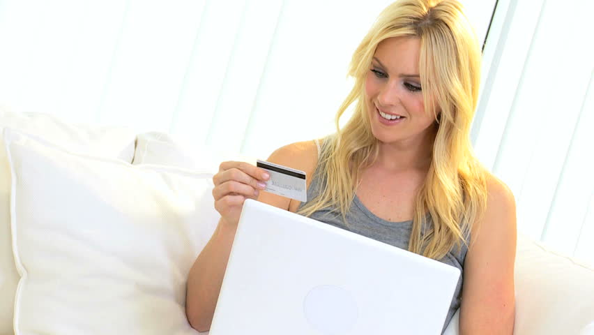 Blonde Caucasian girl relaxing home sofa shopping laptop online with credit card