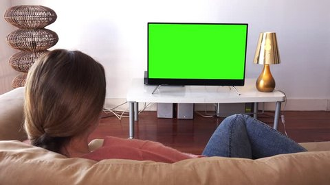 Young Woman Relaxed At Home Watching TV. Girl watching green screen television lying down on the couch