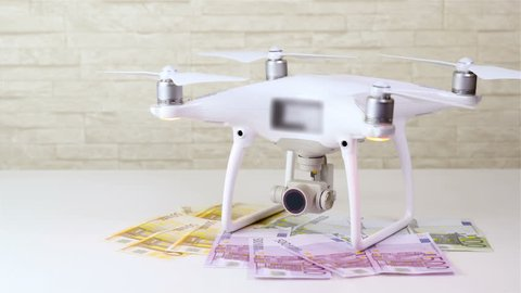 Drone on pile of money 4K. Static shot of white quadcopter in focus standing on Euro banknotes with few more falling over from above. White table. Drone lights blip.