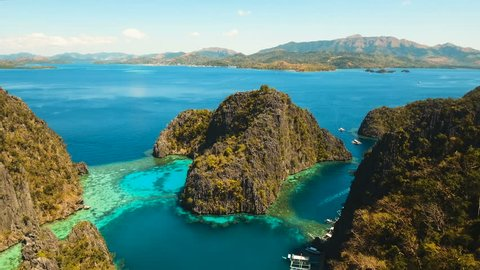 Tropical lagoon with azure water, beach by the Kayangan Lake, Philippines. Aerial view Coron island, with cove, bay at Kayangan lake. Lagoon with sailing boats. Aerial video. Philippines. 4K video