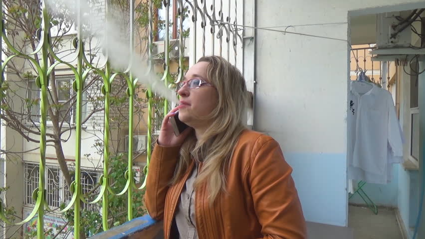 A girl in an orange jacket smokes an electronic cigarette and talks on her mobile phone. Brown jacket. Smoke hits a video camera.