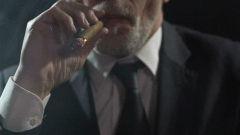 Overbearing oligarch enjoying cigar smoking, authority and power, slowmotion