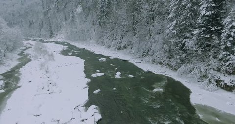 4K. AERIAL VIEW. Mountain river in winter. Snowy winter in the mountains. Flight over the icy mountain stream. A fast mountain river. Ice   Carpathian ukraine