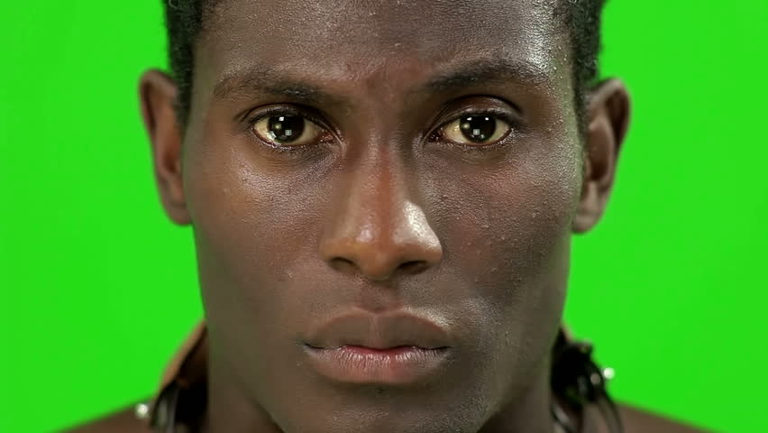 african young guy facing to the camera with a strong look in a chroma key