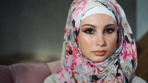 A young Muslim woman in a beautiful headscarf, called a hijab, looks at the camera. A modern Arab woman with brightly colored eyes slowly blinks