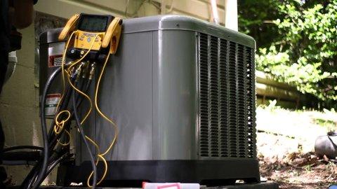 HVAC technician runs refrigerant tests on new operational business grade air con