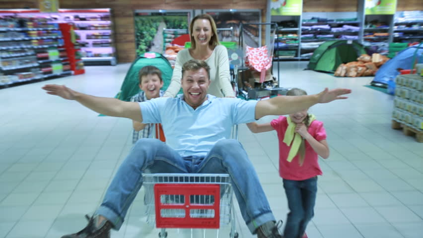 Mom and two kids having fun wheeling daddy around store in the market shopping cart. | Shutterstock HD Video #2707733