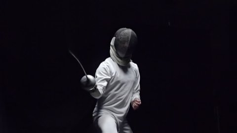 Slow motion shot of professional fencer in protective uniform practicing maneuvers with foil alone in dark studio