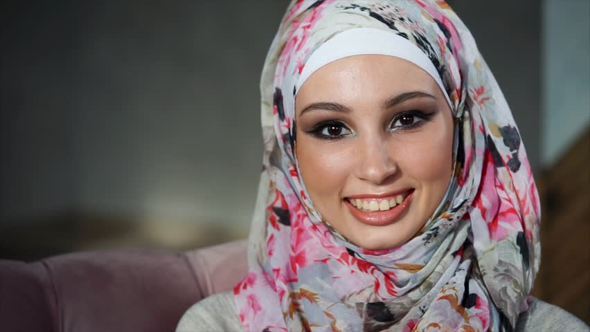 Slow motion close-up shot of a smiling young Muslim woman wearing colorful headscarf. Portrait at home
