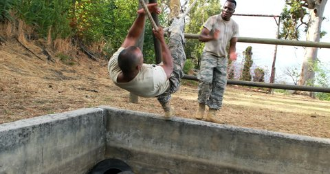 Military soldier climbing rope during obstacle course in boot camp