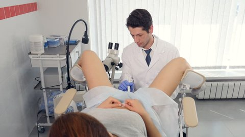 Doctor gynecologist looking into microscope examining female illness. Gynecologist appointment concept.