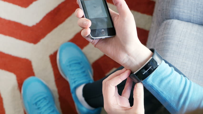 PARIS, FRANCE - CIRCA 2017: Athletic sport woman preparing her smartwatch and pairing the mobile smartphone iPhone with Microsoft Band 2 activity tracker for theupcomming run jogging with Strava app