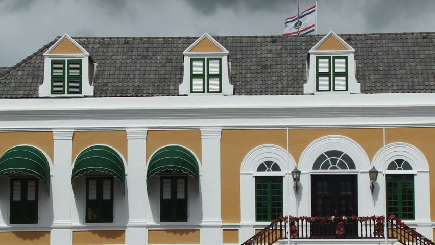 Close up of the facade of the governors palace in Willemstad, Curacao with the Curacao flag flying above