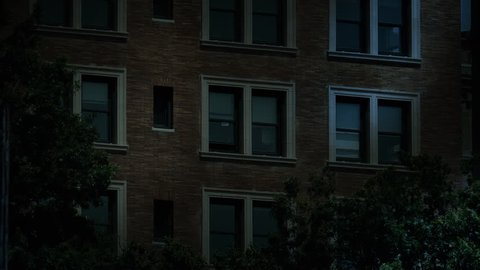 "A typical New York style apartment or office building establishing shot at night with the lights from a window turning on then off. Simulated ""day-for-night"" composite."