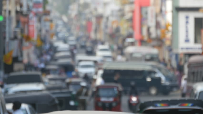 Blurred unrecognizable people are walking around city center. Cars drive on roads in the town. Out of focus is backdrop of bustling big city with busy traffic #27185293