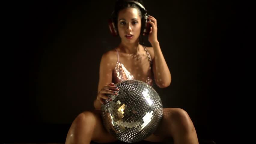 a sexy gogo dancer shot in a studio holding a discoball