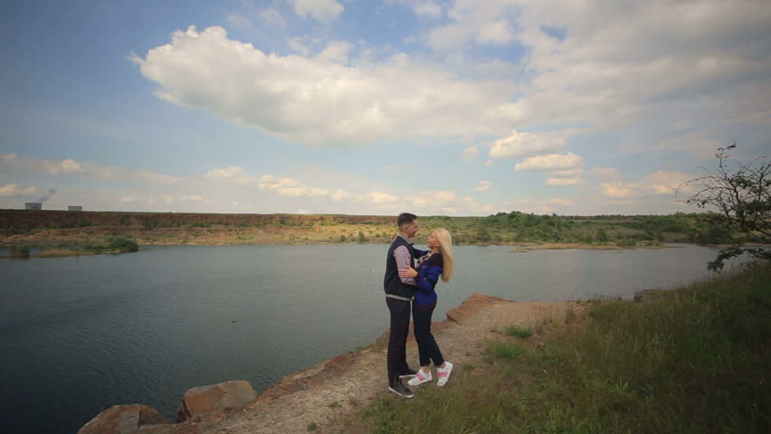 Young man and woman embrace and kiss while standing near a large lake. Couple in love hugging against the background of beautiful views of nature. #27188836