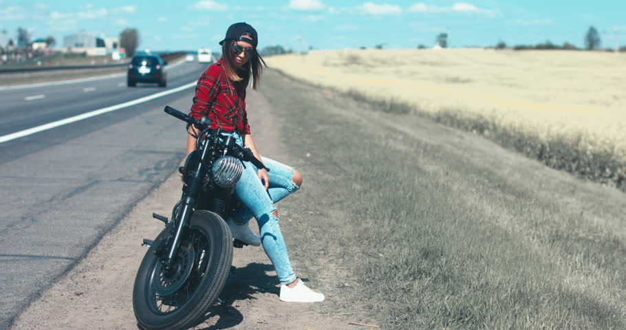 CINEMAGRAPH - seamless loop. Young Caucasian girl with brown hair sits on a motorbike near a road. 4K UHD RAW edited footage