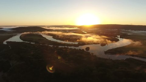 River valley heart bent early morning fog clouds Primorye, Vladivostok. Flight to yellow orange sunrise horizon. Wide open space Aerial drone drift beautiful Russian nature landscape.