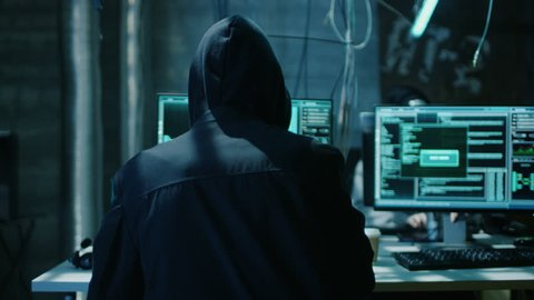 Hooded Hacker Breaks into Corporate Data Servers and Infects them with Virus. His Hideout Place has Dark Atmosphere, Multiple Displays, Cables Everywhere. Shot on RED EPIC-W 8K Helium Cinema Camera.