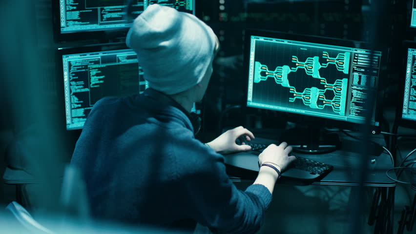 Back View of Teenage Hacker Infecting with Virus Data Servers of Government. His Hideout is Dark with Many Monitors Around. Shot on RED EPIC-W 8K Helium Cinema Camera. | Shutterstock HD Video #27244663