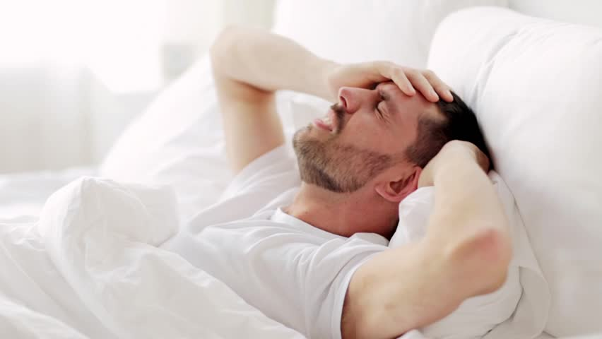 hangover, sleeping and people concept - man with headache waking up in bed at home