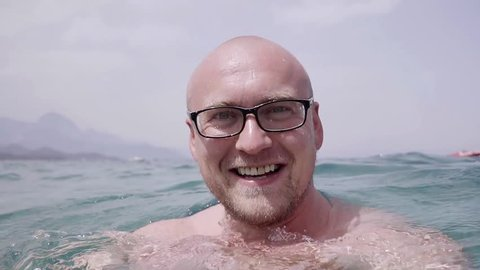 Happy bald man with glasses floating in the sea water and shows a gesture with his finger at the camera. Close-up slow motion.
