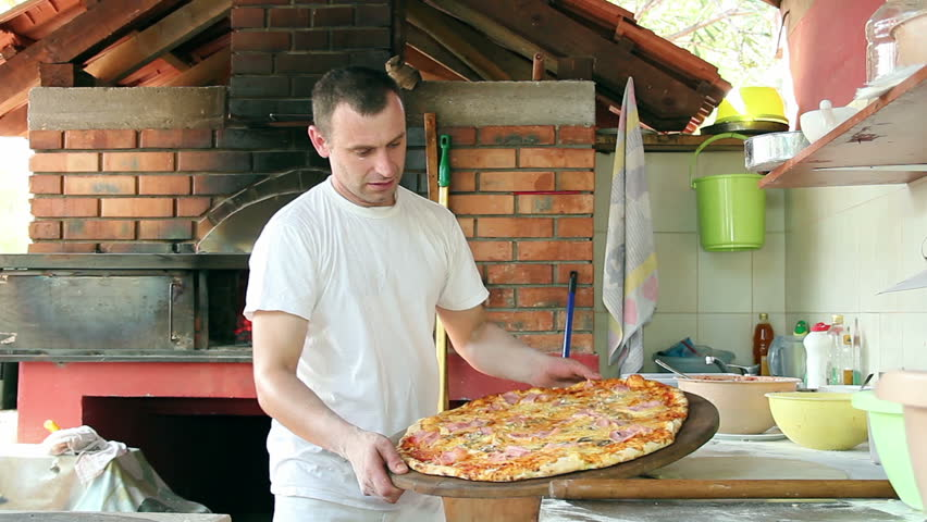 Portrait of a pizza chef holding large family pizza. HD1080p.