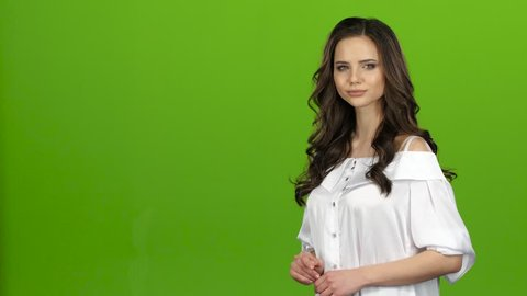 TV presenter tells everyone about the weather, she is smart and beautiful. Green screen