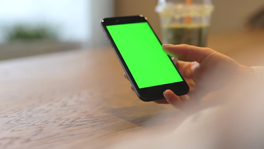 Woman browsing one finger green screen on mobile phone in cafe shop. Handheld video with female and chroma key smartphone display. Used mobile phone for copy past advertising or game design template | Shutterstock HD Video #27269653