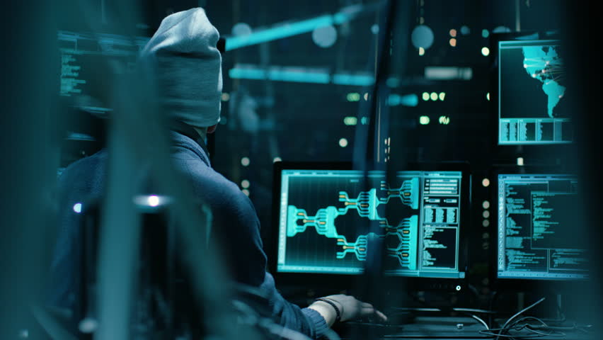 Back View of Teenage Hacker Infecting with Virus Data Servers of Government Infrastructures. His Hideout is Dark with Many Monitors Around. Shot on RED EPIC-W 8K Helium Cinema Camera. RED Cinema 4K.