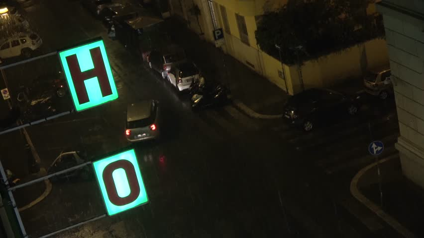 Footage close up from fourth floor looking down out of hotel window on streets during rainy night showing illuminated hotel sign and dark streets cars passing by with lights driving through evening 4k