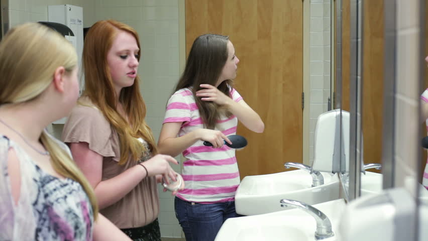 A Few Girls (students) Putting On Makeup While Talking In A School Restroom