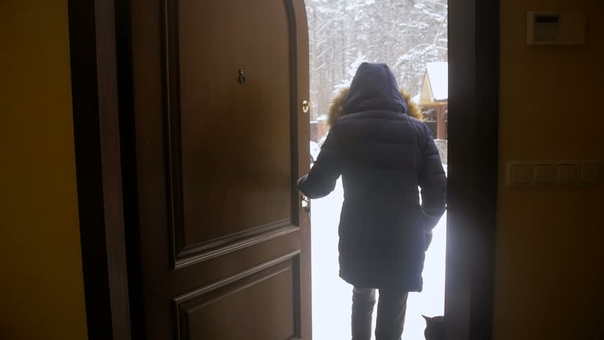 Slow motion video of cheerful girl opening house door and running out on backyard covered with snow