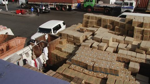 DUBAI, UAE - CIRCA 2008: Pan-right high-angle shot of cargo unloaded at the port. The UAE is home to Jebel Ali - the world's 9th busiest port and the largest man-made harbour.