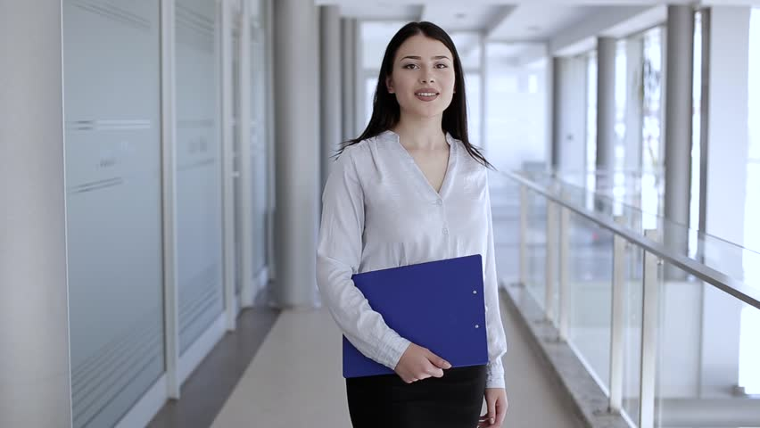 Attractive woman walking and holding paperboard,stops and smile to camera | Shutterstock HD Video #27393763