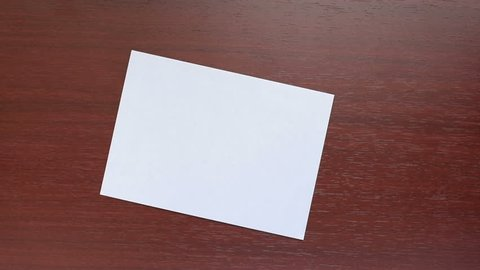 Man's hand with white an envelope on a dark wooden  background. Hand giving a blank letter. Correspondence. Business concept. Hand with blank envelope.