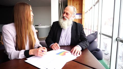 Old Businessman Shakes Hands, Signs of Paper. Successful Gray Old Businessmen Makes Deal With Young Woman in Big Company Representation in Autumn. Beautiful Stately Grey Head Man With Long Beard