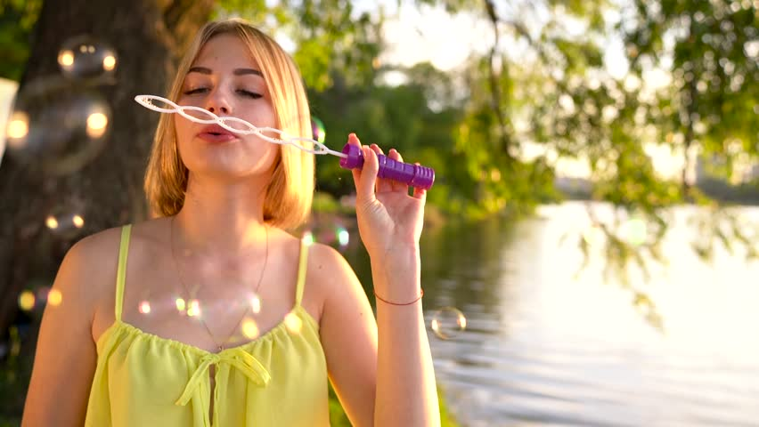 Young beautiful blonde blowing soap bubbles outdoors - slow motion