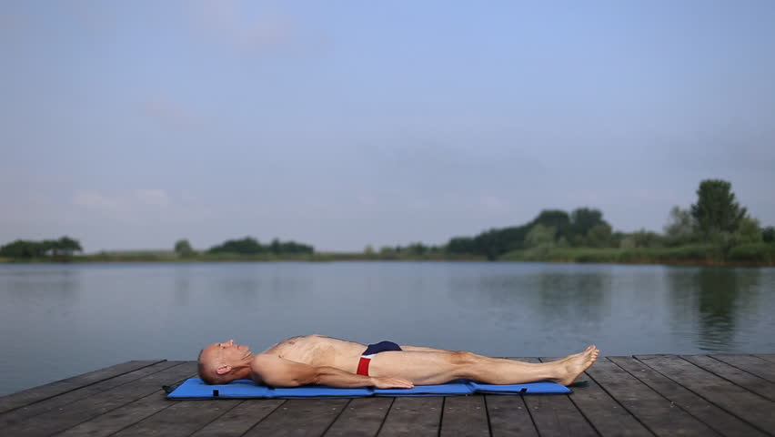 A man in swimsuit doing yoga, shoulder stand pose, outdoor on blue yoga mat in the quiet scenery by the lake / A man doing yoga by the lake | Shutterstock HD Video #27451783