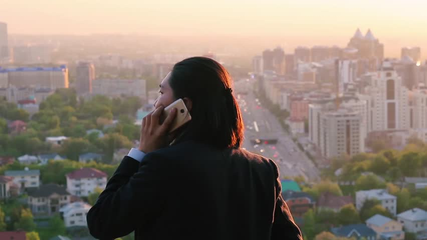 Wealthy businessman negotiating a deal on a phone and gazing at a marvelous city landscape | Shutterstock HD Video #27478363
