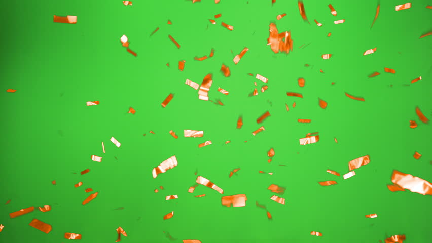 Real Confetti falling soft and beautiful in orange and with Green screen for party and celebrations like victories and birthdays or advertising