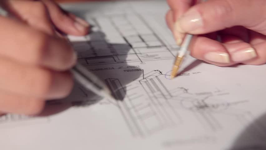 Circular tracking close-up shot of hands drawing plans