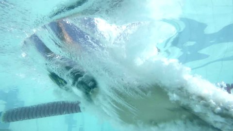 Slow-motion underwater CU of swimmer diving