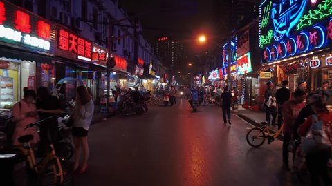 SHANGHAI MAY 2017: Shanghai shouning rd xiaolongxia food street at night. Walking through downtown Asia urban center with street side seafood restaurants, on bustling busy street with many neon signs.