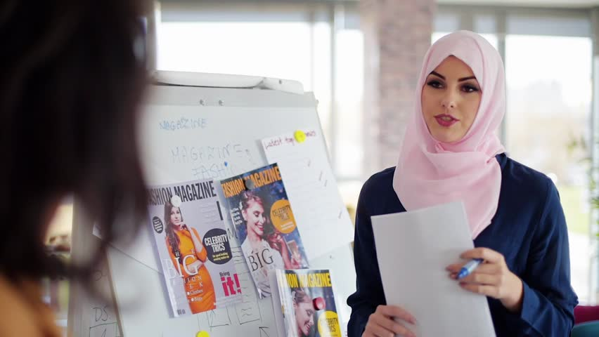 Muslim business woman over talking about fashion magazine. Covers magazine visible on the video are our project and have proper PR.