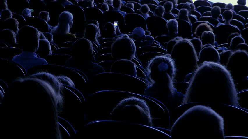 Spectators watch the show or view in the theater. Video from the back. Children and adults alike. Clip footage in 4K.
