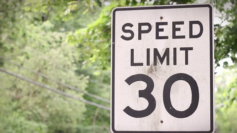 Camera pans to Speed Limit 30 sign near forested road